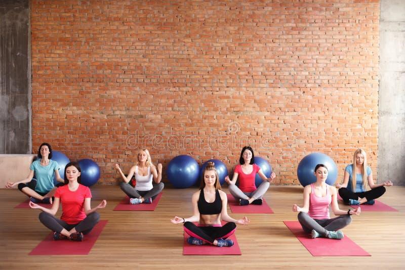 Gladlynta slanka flickor gör yoga arkivbild