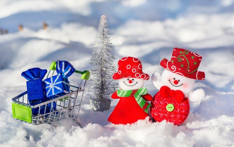 Gladlynta snögubbear på en silvrig trädbakgrund för nytt år med en spårvagn som är full av julleksaker i snön på snön royaltyfri fotografi
