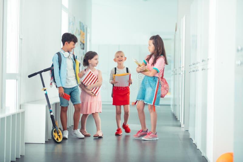 Gladlynta stilfulla barn som tillsammans går till klassrumet royaltyfria foton