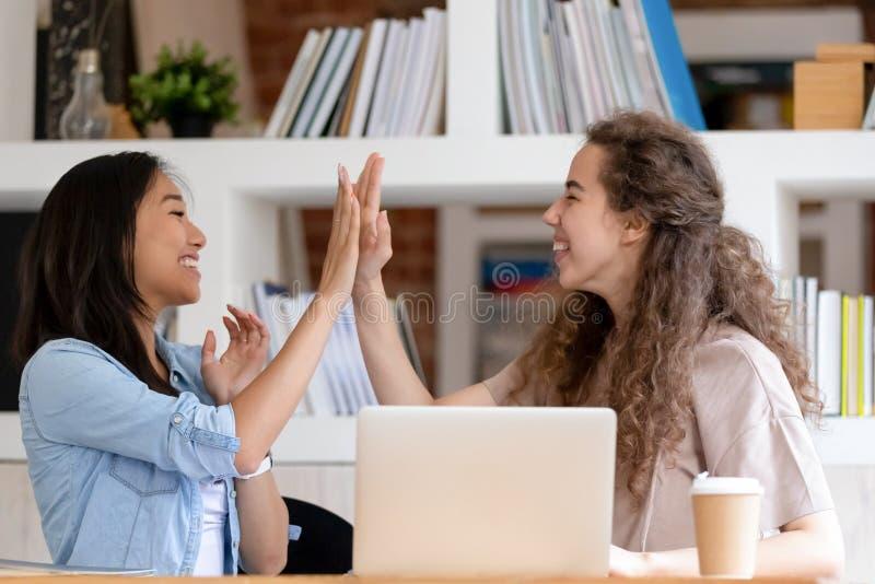 Gladlynta studentflickor känner sig lyckliga fira framgång som ger högt fem royaltyfri bild