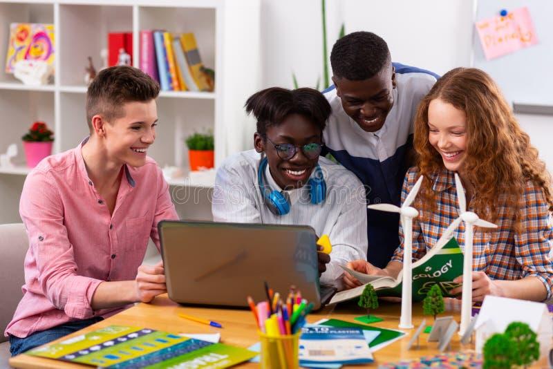 Gladlynta tonåringar som känner sig glade, medan studera ekologi tillsammans arkivbild