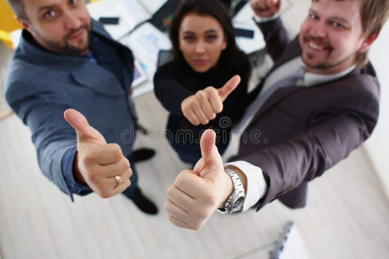 Gladlynta unga affärsmän har stora fingrar för framgångresultatshow royaltyfria bilder