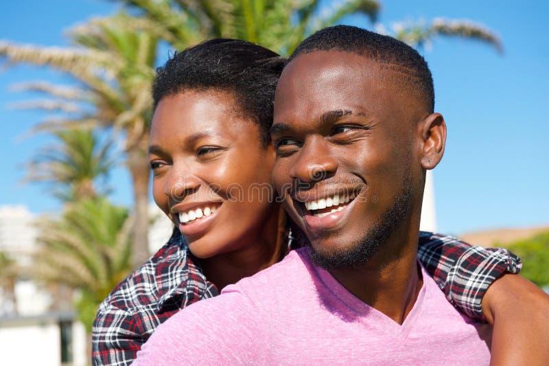 Gladlynta unga afrikansk amerikanpar som utomhus ler royaltyfria bilder