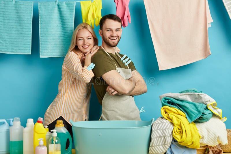 Gladlynta unga par är lyckliga, som de har avslutat hushållsarbete royaltyfri bild