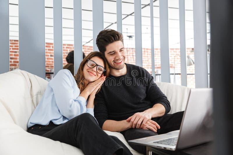Gladlynta unga par av kollegor som tillsammans arbetar royaltyfri fotografi