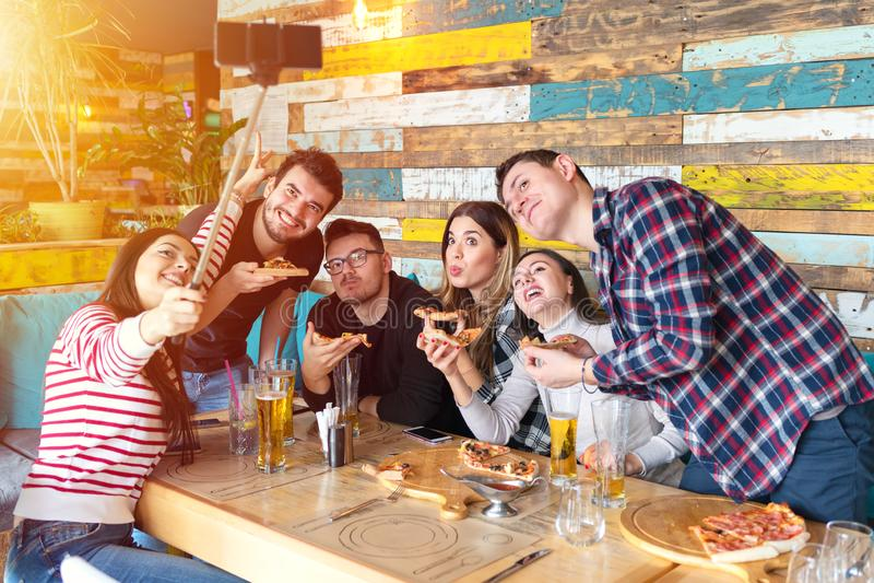 Gladlynta unga vänner som tar selfie med den smarta telefonen, medan dela en pizza på stångrestaurangen arkivbilder
