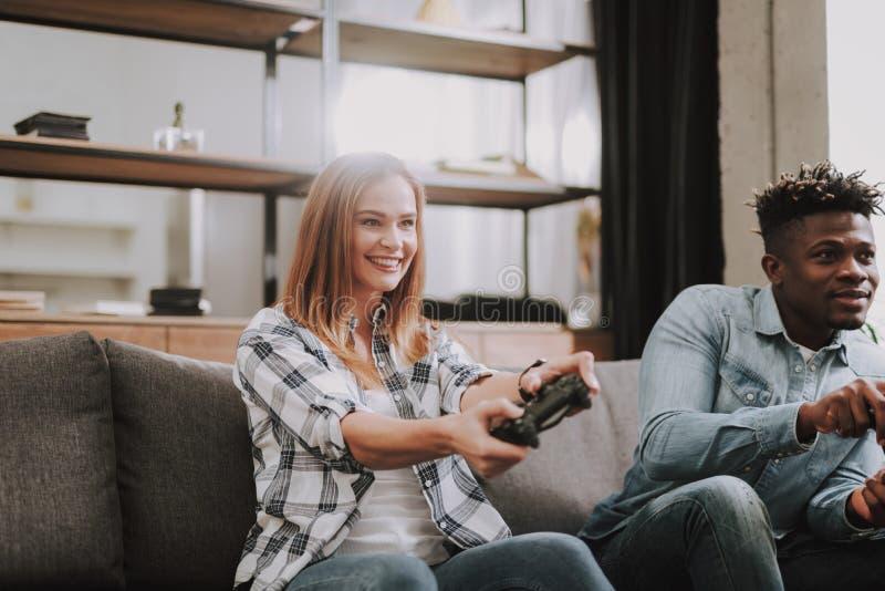 Gladlynta unga vänner som hemma spelar videospel arkivfoto