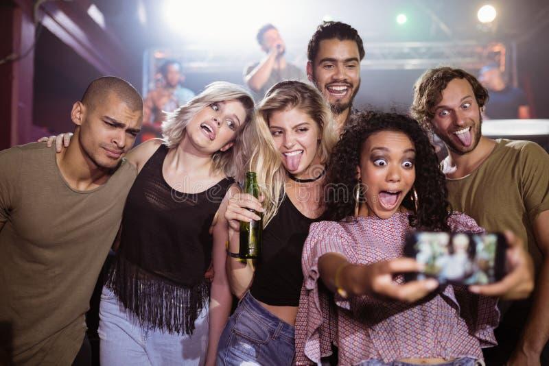 Gladlynta unga vänner som talar selfie på nattklubben royaltyfri foto