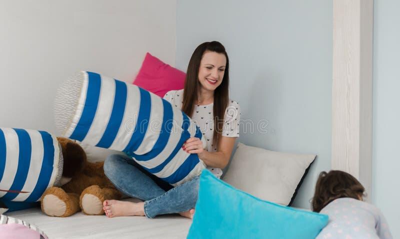 Gladlynta ungar och föräldrar som har kuddekamp på säng hemma fotografering för bildbyråer