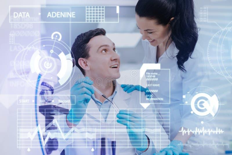 Gladlynta vänliga kollegor som ler, medan arbeta med blodprövkopior arkivbild