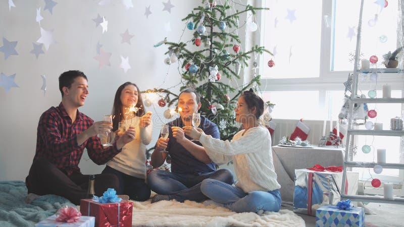 Gladlynta vänner dricker champagne och bränner tomtebloss under firar nytt år eller julafton och att ha stor tid arkivbilder