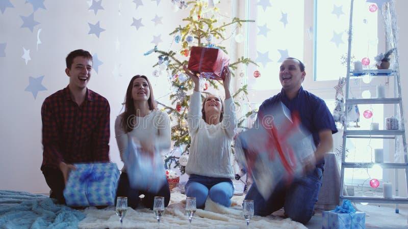 Gladlynta vänner kastar och fångar askgåvorna gåvor flyger in i deras händer Gladlynta vänner firar jul fotografering för bildbyråer