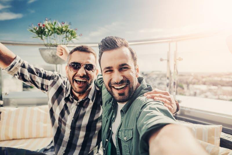 Gladlynta vänner på utomhus- kafédanandeselfie arkivfoton