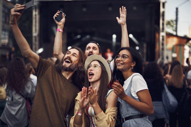 Gladlynta vänner som gör selfie på den utomhus- musikfestivalen fotografering för bildbyråer