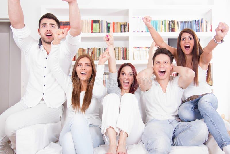 Gladlynta vänner som håller ögonen på fotbollleken på tv royaltyfria bilder