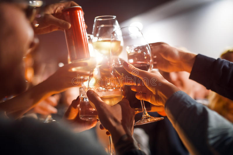 Gladlynta vänner som klirrar exponeringsglas ovanför matställetabellen Alkohol och rosta, parti- och berömtema Lyckönskan arkivbilder