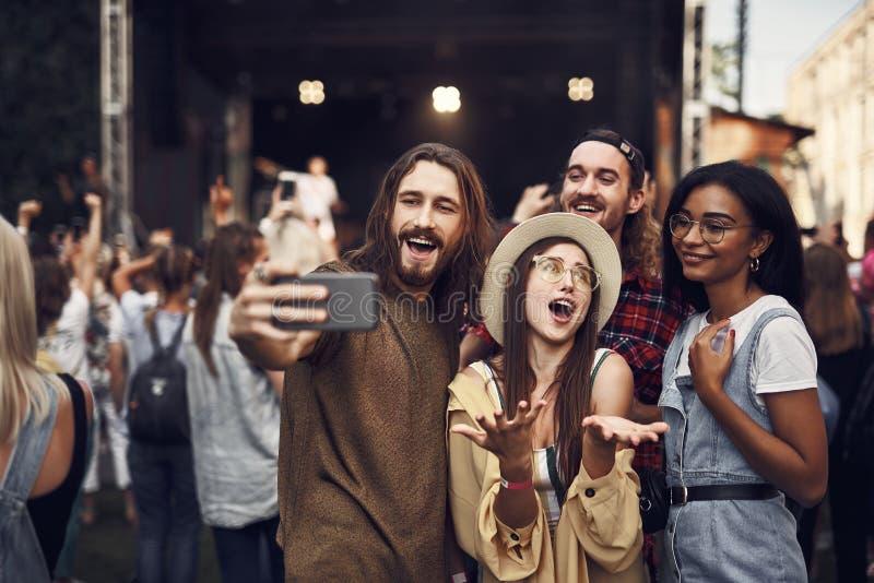 Gladlynta vänner som tar selfie, medan spendera tid på den utomhus- musikfestivalen royaltyfri foto