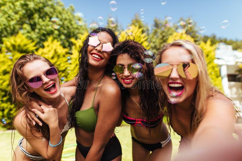 Gladlynta vänner som tar selfie på poolsiden royaltyfria bilder