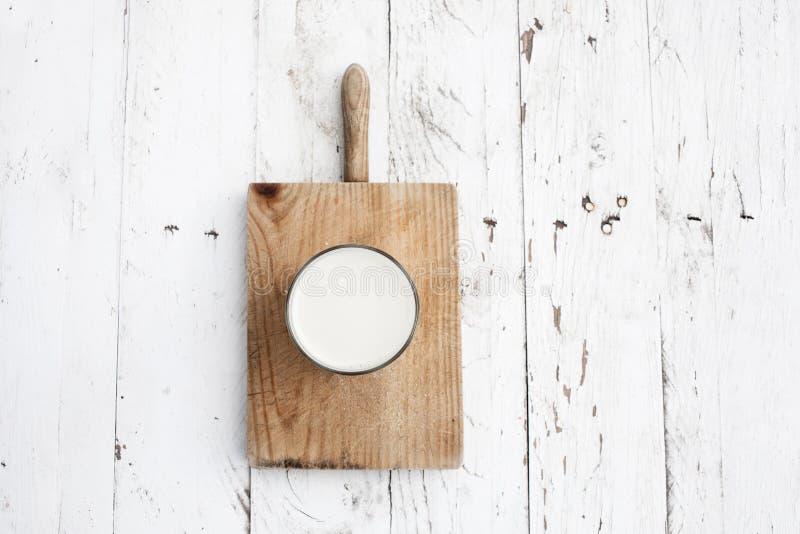 Glads mleko na nieociosanym białym drewnianym stole Zdrowy śniadanie, zdjęcie stock