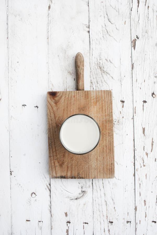 Glads mleko na nieociosanym białym drewnianym stole Zdrowy śniadanie, zdjęcia stock