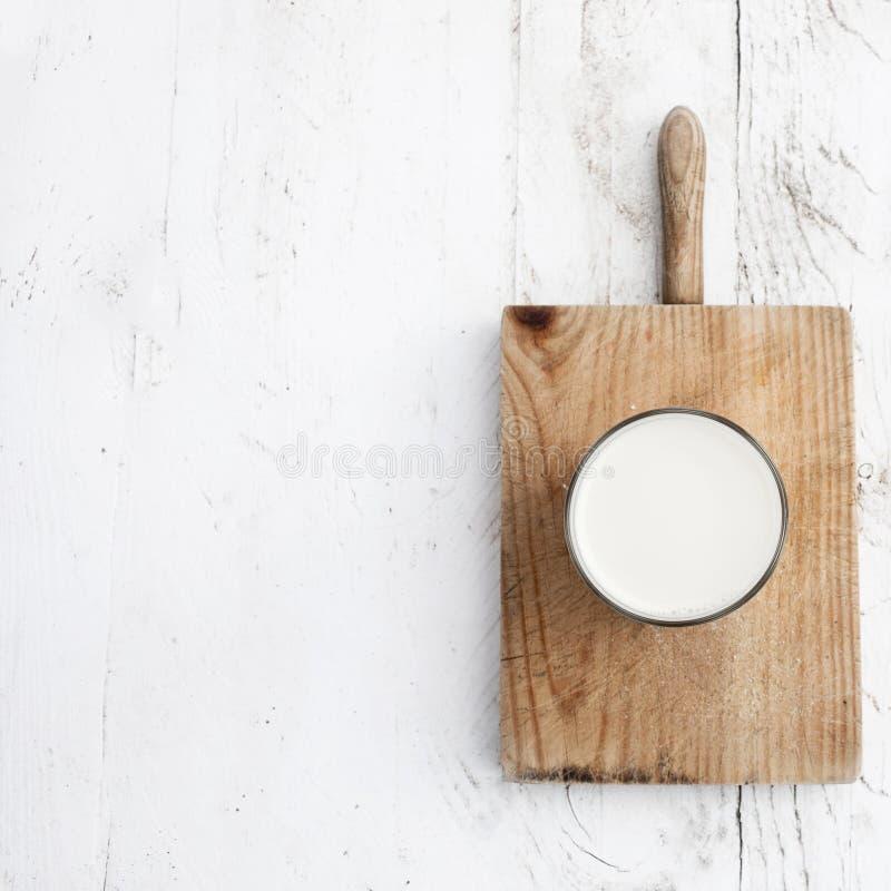 Glads mleko na nieociosanym białym drewnianym stole Zdrowy śniadanie, fotografia stock