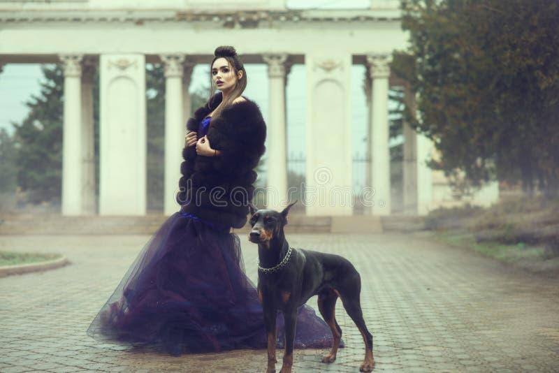 Glam dam som bär för aftonkappa för lyxig paljett det violetta anseendet och för pälslag på gränden i parkera med hennes Doberman royaltyfria bilder