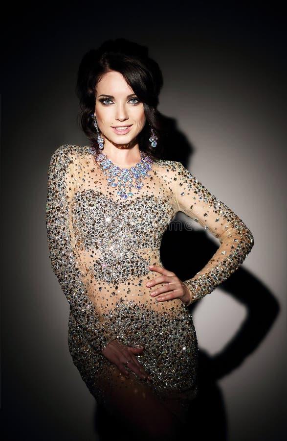 Glam. Senhora bem sucedida no vestido de noite de prata sobre o preto fotografia de stock