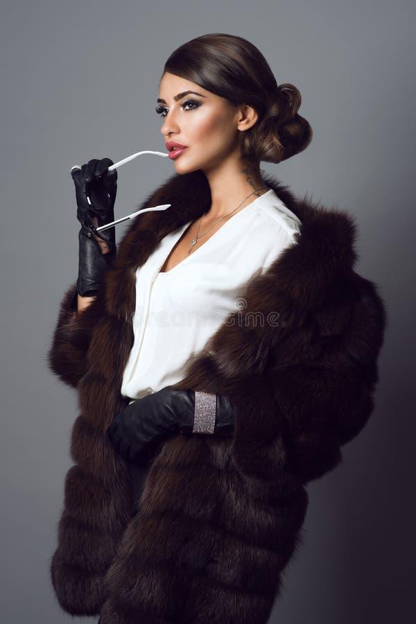 Glammodel die juwelen en sabelmarterlaag met zonnebril in haar hand dragen royalty-vrije stock afbeeldingen