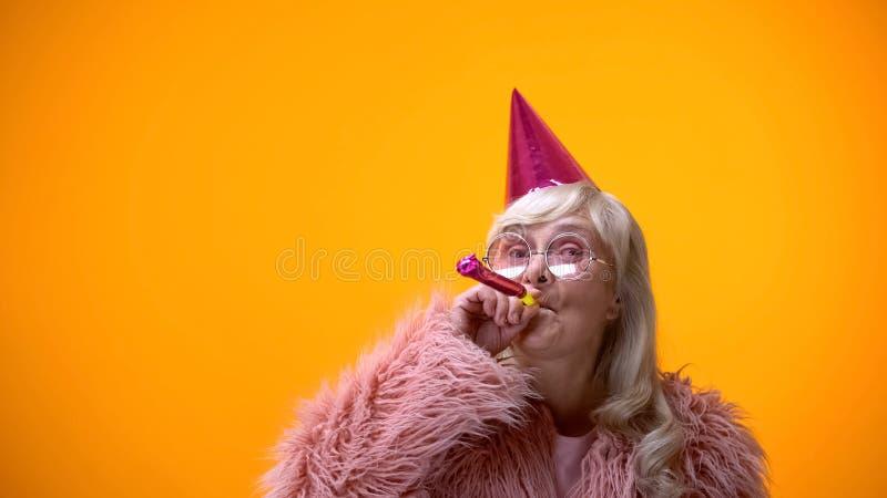 Glamorös åldrig kvinna som blåser partihornet som firar födelsedagårsdag royaltyfria foton