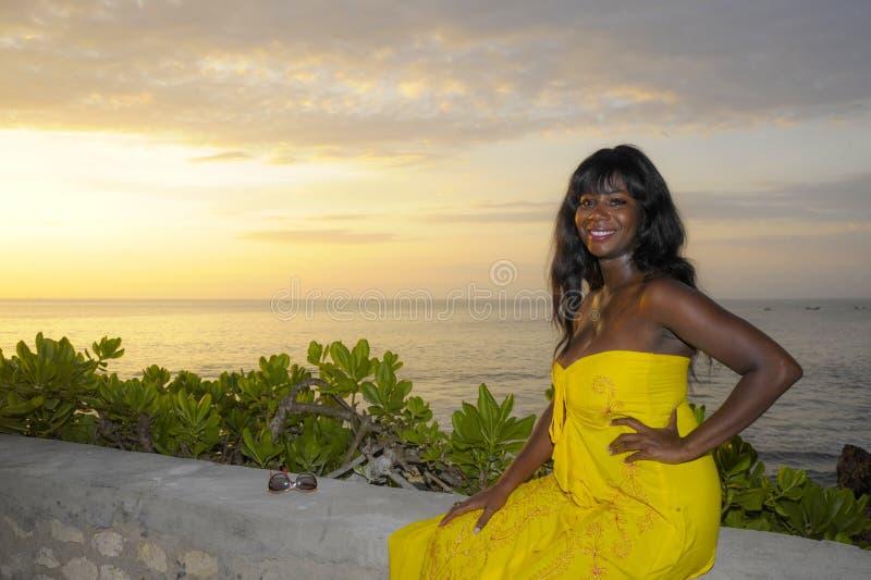 Glamorös afrikansk amerikansvart kvinna i chic och elegant posera för sommarklänning som kopplas av på sommarsolnedgångstranden fotografering för bildbyråer