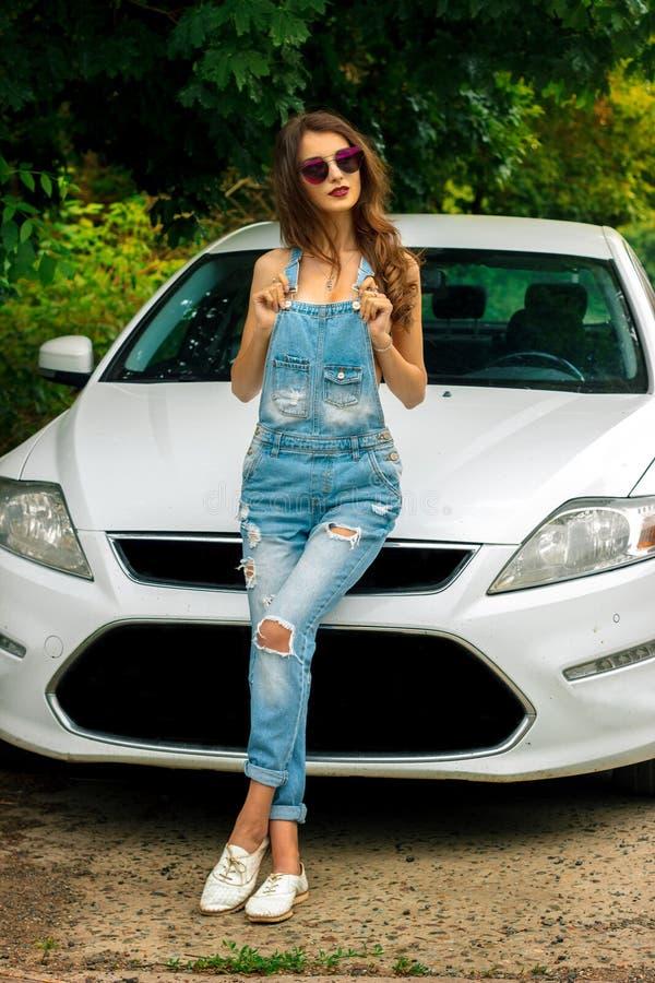 Glamorös brunett som poserar nära den vita bilen royaltyfri foto