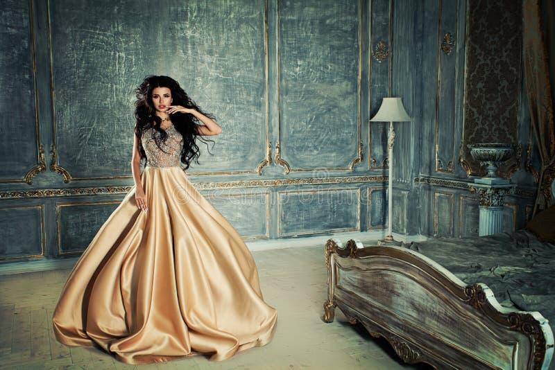 Glamorös brunettkvinna i ett sovrum royaltyfri bild