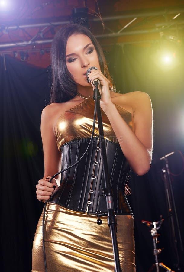 Glamorös flicka som sjunger på etappen royaltyfri bild