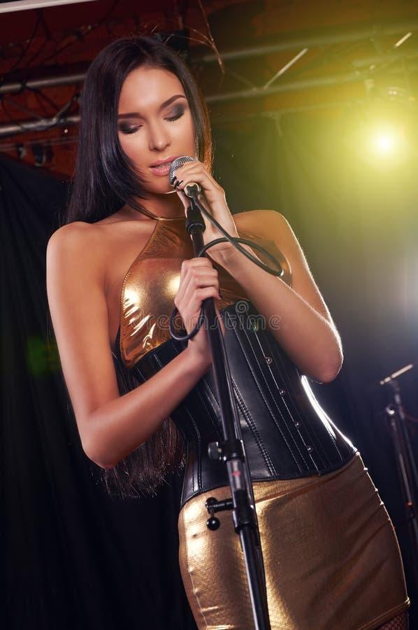 Glamorös flicka som sjunger på etappen arkivfoto