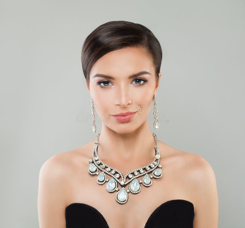 Glamorös kvinna för modemodell med kort hår, makeup och diamantsmycken, stående royaltyfri bild