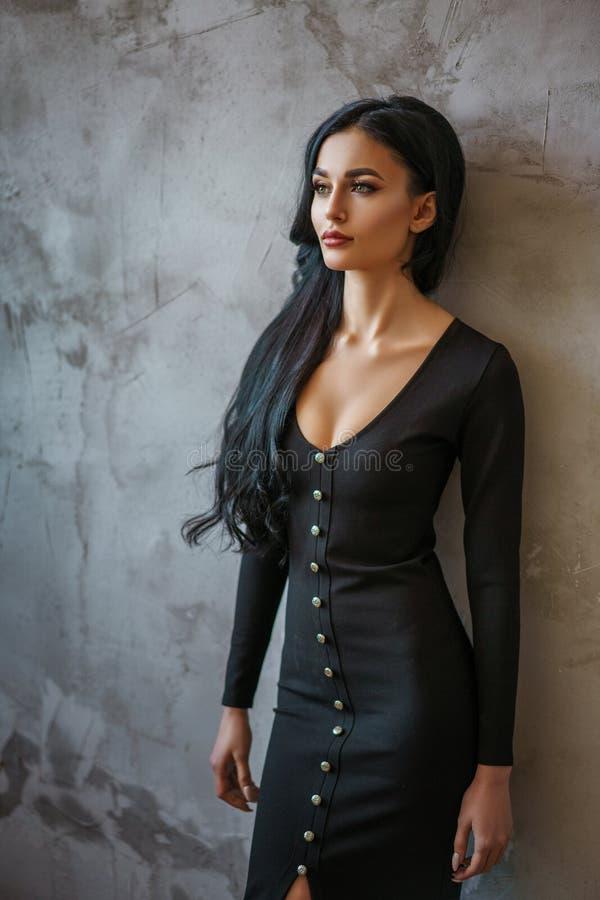 Glamorös kvinna i svart klänning på grå väggbakgrund, härlig framsida och ljust smink royaltyfria foton