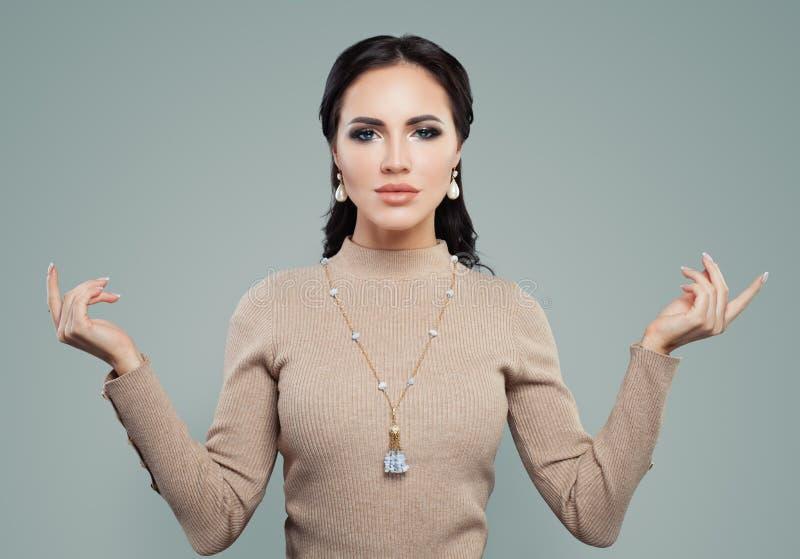 Glamorös kvinna med makeup, pärlaörhängen och halsbandet Smyckenmodellstående arkivbild