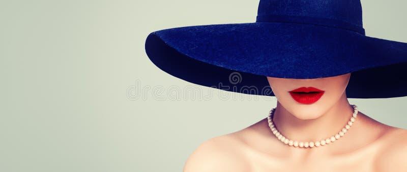 Glamorös kvinna med röd kantmakeup, den eleganta hatten och pärlor, retro stående för tappning royaltyfria foton