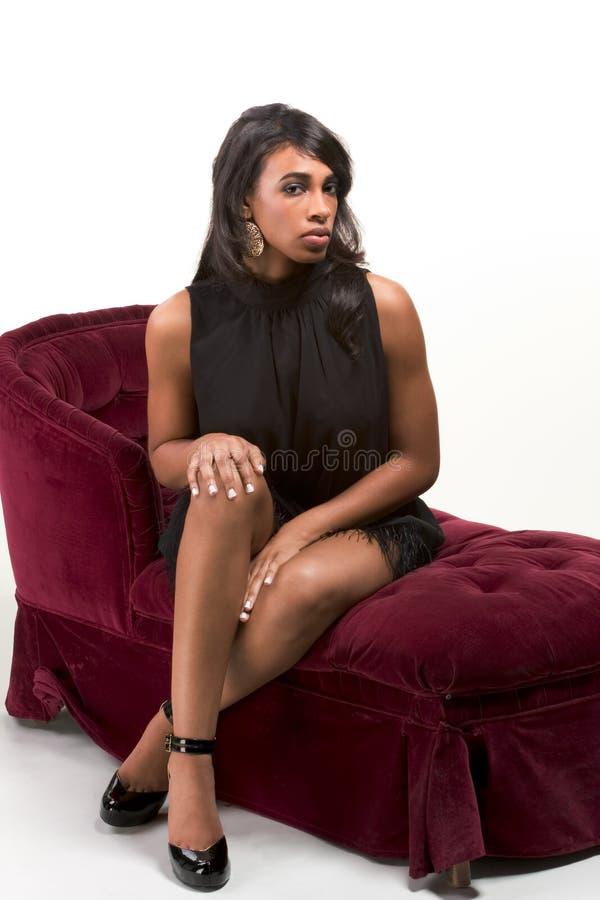 glamorös model röd kvinna för afro amerikansk soffa arkivfoto