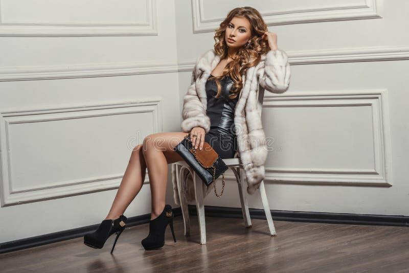 Glamorös stående av den unga härliga kvinnan i läderkängor och stilfull handväska arkivbild