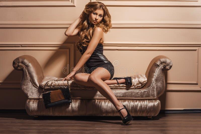 Glamorös stående av den unga härliga kvinnan i läderskor och stilfull handväska arkivbilder