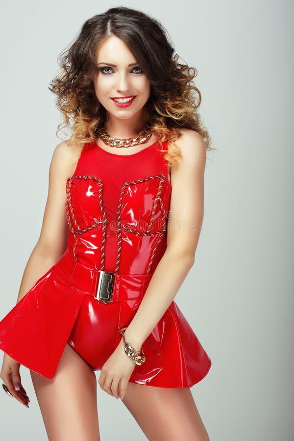 glamor 红色发光的衣裳的微笑的肉欲的妇女 免版税库存照片