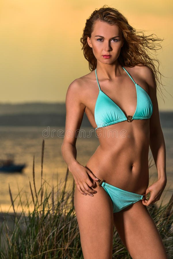 Glamor beautiful stylish blond Caucasian young woman model with perfect tanned body in blue swimsuit on the beach. stock photo