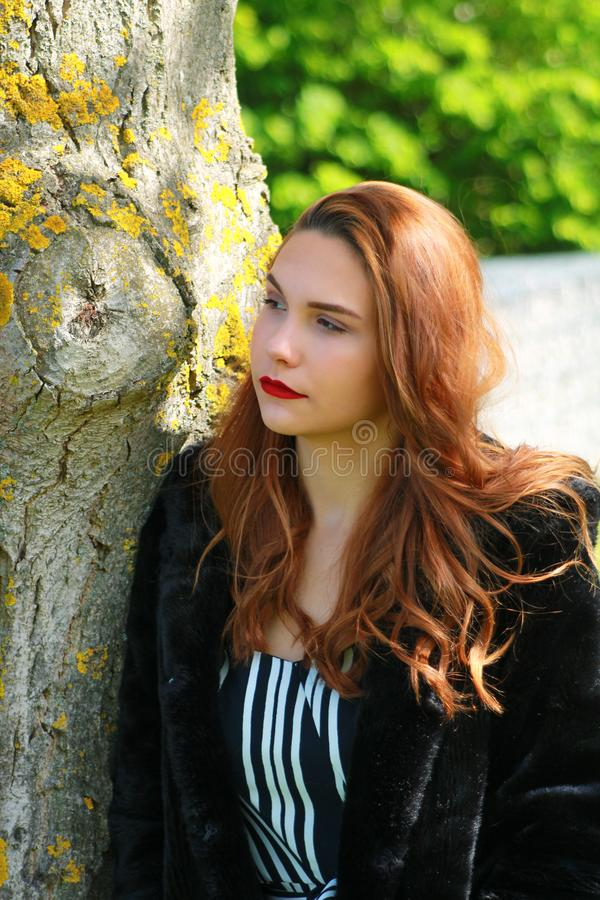 Glamor girl wearing makeup with long red hair and red lipstick royalty free stock photo