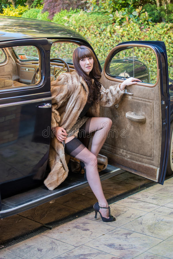Glamor model wearing a fur coat and stockings stock photos