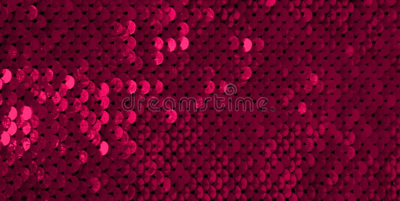 Glamor Red Background with Sequins. Close-up. Abstract Texture scales with shiny maroon sequins on fabric, macro. Beautiful Holiday Wallpaper with pattern of stock photos