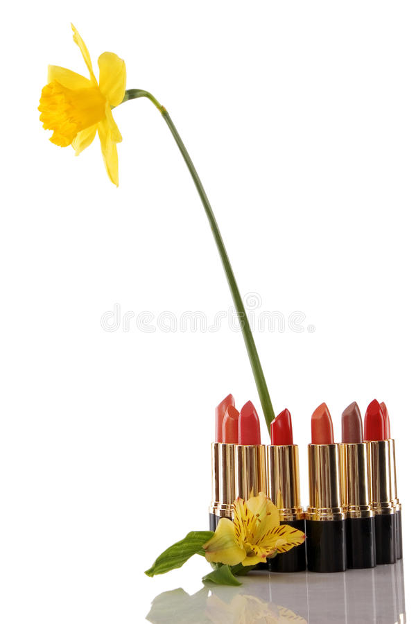 Glamor red shiny lipstick and yellow flower royalty free stock photo