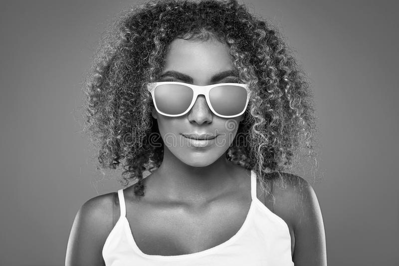 Glamor swag black hipster woman model with curly hair. Sensual smiling portrait of glamor swag black hipster woman model with curly hair and sunglasses posing on royalty free stock photos