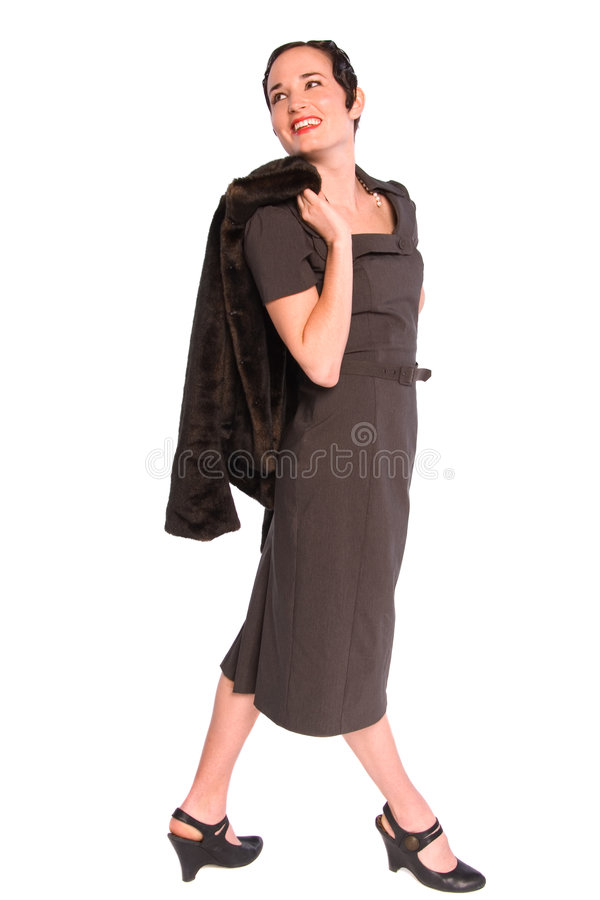Glamorous 1920s woman. Glamorous 1920s style woman holding a fur coat, and looking over her shoulder smiling. Isolated on white stock photography