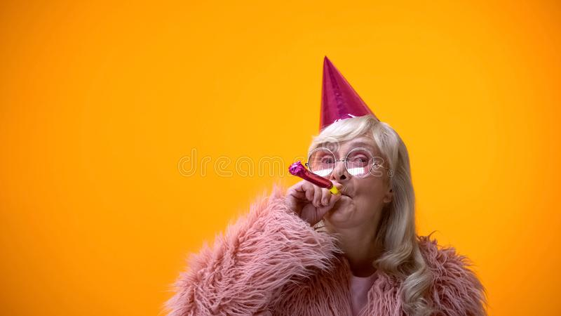 Glamorous aged woman blowing party horn, celebrating birthday anniversary royalty free stock photos